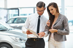 Young Woman Signing Documents at Car Dealership with Salesman.  stock images