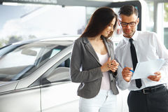 Young Woman Signing Documents at Car Dealership with Salesman.  Royalty Free Stock Images