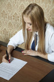 Young woman signs a contract Royalty Free Stock Image