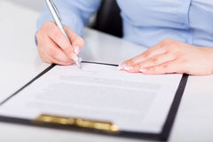 Young woman signs a contract Royalty Free Stock Images