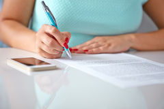 Young woman signs a contract Royalty Free Stock Photos