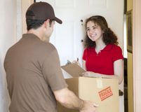 Young Woman Signs for Delivery Stock Photo