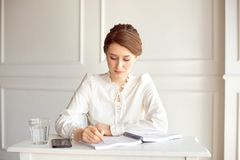 Young woman signs important documents while sitting at her desk in an office. Pretty Caucasian female working in a home royalty free stock image
