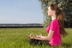 Young woman siiting on the grass in yoga pose Royalty Free Stock Images