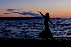 Young woman silhouette against sunset ocean. Stock Photos