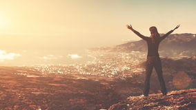 Young woman silhouette with arms up standing on the mountain peak stock video