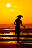 Young woman silhouette on the beach in summer Stock Photos