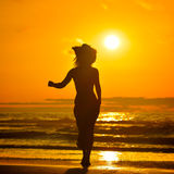Young woman silhouette on the beach in summer Stock Image