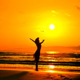 Young woman silhouette on the beach in summer sunset Royalty Free Stock Images