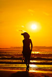Young woman silhouette on the beach at sunset Stock Photos