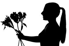 Young woman silhouette giving flowers Stock Image