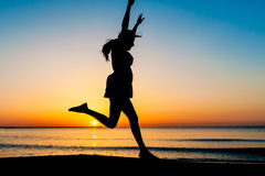 Young woman silhouette jumping on the beach Royalty Free Stock Photo