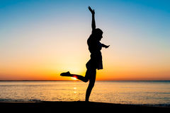 Young woman silhouette jumping on the beach Royalty Free Stock Image