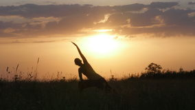 Young woman silhouette practicing yoga in front of beautiful summer sunset, Fruska gora, Novi Sad, Serbia. Woman silhouette practicing yoga in front of stock video