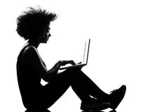 Young woman silhouette siting on floor computing l Royalty Free Stock Images