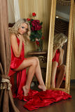 Young woman with silk red cloth. Young beautiful blonde woman covered with silk red cloth sits on bed in the bedroom Royalty Free Stock Image