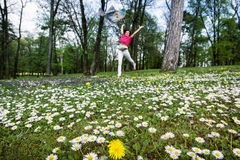 Young woman with silk scarf is jumping on the meadow full of ox-eye daisies and dandelions stock photo