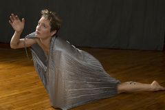 Young woman in silver dress dancing in the studio. Contemporary young woman dancer with short hair, immersed in a silver bag dress, gesturing from inside with Stock Photography