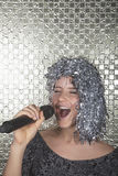 Young woman in a silver wig holding microphone and singing. Young women in a silver wig holding microphone and singing stock images