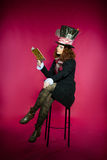 Young woman in the similitude of the Hatter reading book sitting Stock Photos