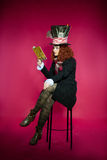 Young woman in the similitude of the Hatter reading book sitting Royalty Free Stock Photo