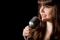 Young woman sing in microphone isolated on black Royalty Free Stock Photo