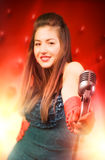 Young woman singer. Retro style. Focus on microphone royalty free stock images