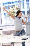 Young woman singing in bright office. Using receiver as microphone, having fun, enjoying herself stock photos