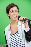Young Woman Singing While Holding Microphone Stock Photo