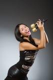 The young woman singing in karaoke club Stock Photo