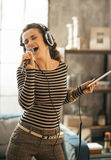 Young woman singing karaoke in loft apartment Stock Photos