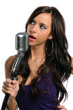 Young Woman Singing Into a Microphone Royalty Free Stock Photo