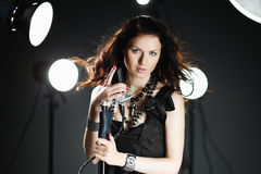 Young woman singing with microphone. With back light and flying hair stock images