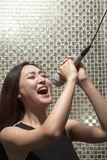 Young woman singing into a microphone at karaoke, shiny background Royalty Free Stock Photos