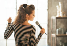 Young woman singing with microphone Stock Image