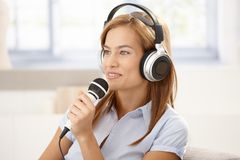 Young woman singing with microphone smiling Stock Images
