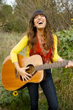 Young Woman Singing and Playing Guitar Stock Image