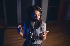 Singer recording song for her album in studio stock images