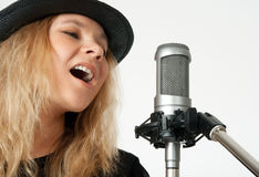 Young woman singing with studio microphone. Young woman in black hat singing with studio microphone. Isolated on white background royalty free stock photo