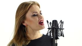 Young woman singing with studio microphone. stock video