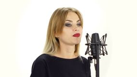 Young woman singing with studio microphone. stock video footage