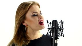 Young woman singing with studio microphone stock video footage
