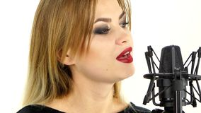 Young woman singing with studio microphone stock video