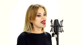 Young woman singing with studio microphone stock footage