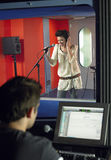 Young Woman Singing With Studio Technician In Foreground. Young female singer with studio technician in foreground at the recording studio royalty free stock photo