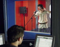 Young Woman Singing With Studio Technician In Foreground. Young female singer with studio technician in foreground at the recording studio royalty free stock image