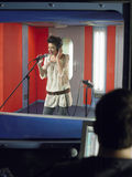 Young Woman Singing With Studio Technician In Foreground. Young female singer with studio technician in foreground at the recording studio stock photography