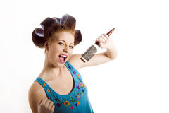 Young woman singing to the brush microphone Royalty Free Stock Images