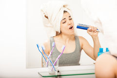 Young woman singing to a hairbrush Stock Photos
