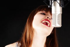 Young woman singing to the microphone in a studio Royalty Free Stock Photo